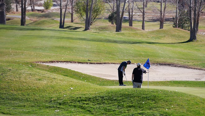 A pair plays golf on Friday at the Aztec Municipal Golf Course.