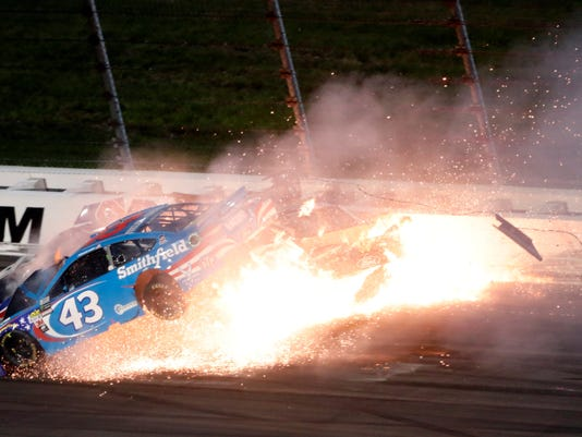 Aric Almirola (43), Danica Patrick and Joey Logano, back left, crash during the NASCAR Monster Cup auto race at Kansas Speedway in Kansas City, Kan., Saturday, May 13, 2017. (AP Photo/Colin E. Braley)