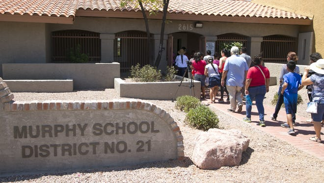 Parents and children walk into the Murphy Elementary School District offices in Phoenix on July 13, 2016. Several dozen parents protested in front of the school-district offices and then went into the offices to attempt to withdraw their children from the district because the parents say their children are not getting an adequate education.
