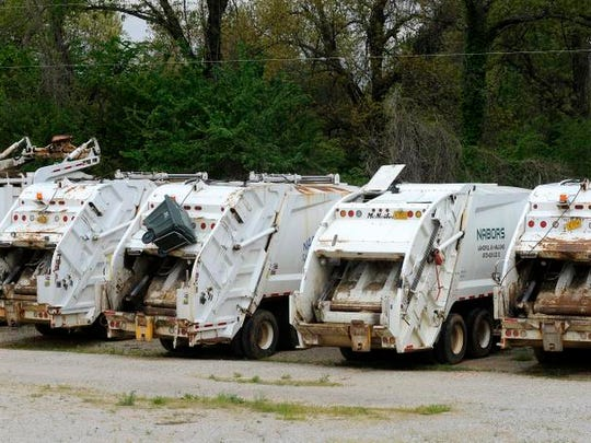 Several NABORS trash-hauling vehicles, formerly owned by Ozark Mountain Regional Solid Waste Management District, sit idle at the NABORS office in Mountain Home in this file photo. The continuing saga of the ill-fated NABORS Landfill continued Friday when retired circuit Judge David Lasure held a hearing concerning the ongoing court battle over an $18 fee imposed to repay bondholders and the Arkansas Department of Environmental Quality for cleanup of the landfill.