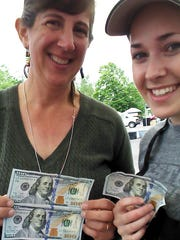 Meg Hebing, left, and her daughter, Lauren Hebing, show off some of the $100 bills signed by Benny that they found during the Salem Saturday Market. Meg Hebing donated several of them to organizations in the Santiam Canyon.