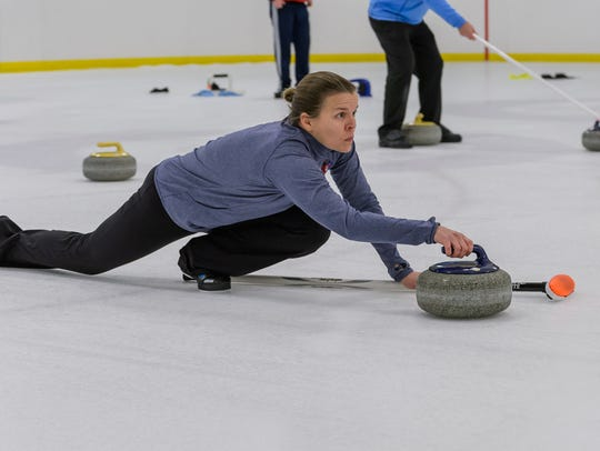 Alison Roark focuses as she slides her stone on her chosen line Tuesday night at The Pavilion.