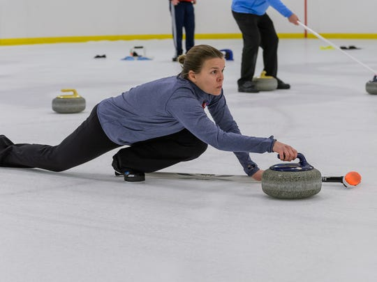 Alison Roark focuses as she slides her stone on the her chosen line Tuesday night at The Pavilion.