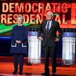 Democratic presidential candidates Hillary Clinton, left, and Sen. Bernie Sanders, I-Vt., stand on stage before a Democratic presidential primary debate at the University of Michigan-Flint on March 6, 2016.