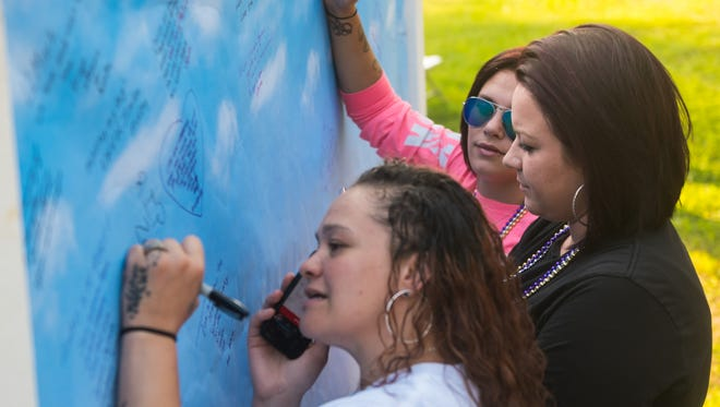 Friends and family of those who have lost someone to addiction write messages to them during Cumberland County's inaugural candlelight vigil for International Overdose Awareness Day at the Cumberland County Fairgounds on Thursday evening.