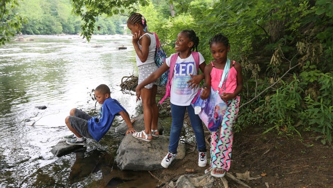 (left to right) Jaheim Lolley, 7, Yamia Brown, 8, Justice Henry, 6, and Keira Bell, 7, play along the Brandywine River while visiting the park with their camp from the Walnut YMCA on Tuesday afternoon.