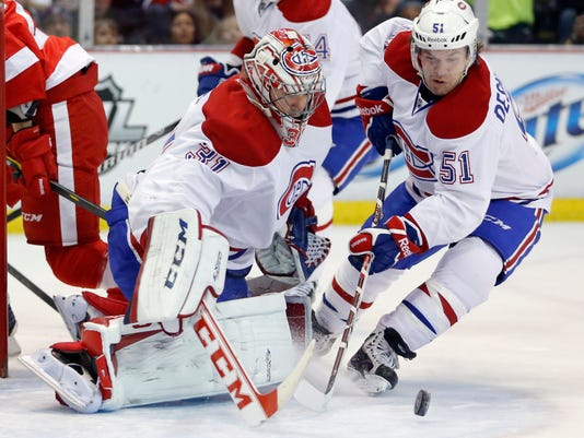 Montreal Canadiens goalie Carey Price (31) receives help stopping a shot from teammate David Desharnais (51) during the first period of an NHL hockey game against the Detroit Red Wings Thursday, March 27, 2014, in Detroit. (AP Photo/Duane Burleson)