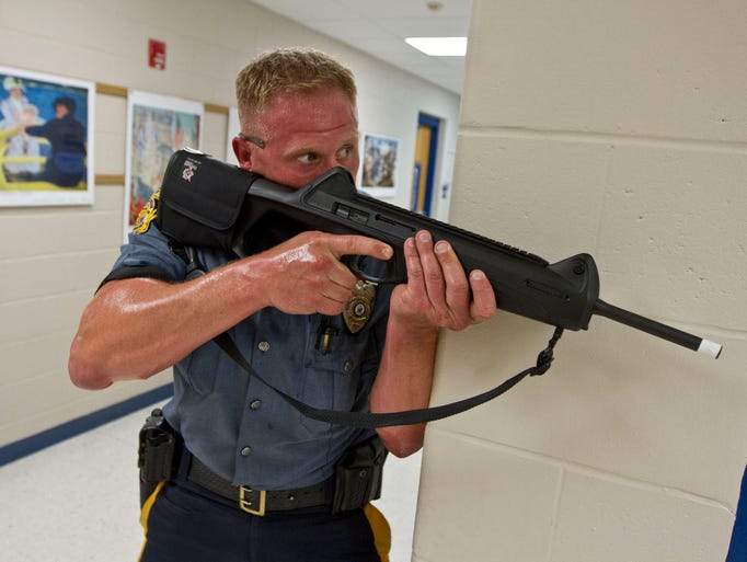 Patrolman Zachary Rhein keeps a hallway secure during the drill. The Ocean Township Police Department holds a lockdown and search drill involving simulated gunfire at the Wanamassa Elementary School. Ocean Township, NJ Wednesday, June 18, 2014 Doug Hood