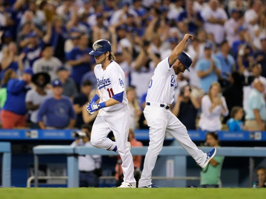 Los Angeles Dodgers' Josh Reddick, left, rounds the bases past third base coach Chris Woodward after hitting a grand slam during the seventh inning of a baseball game against the Colorado Rockies, Saturday, Sept. 24, 2016, in Los Angeles. (AP Photo/Jae C. Hong)