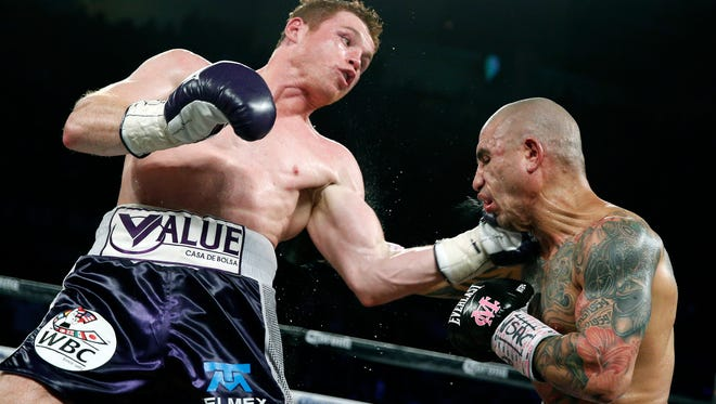 Miguel Cotto (right) get hits by Canelo Alvarez during a WBC middleweight title bout Saturday, Nov. 21, 2015, in Las Vegas.