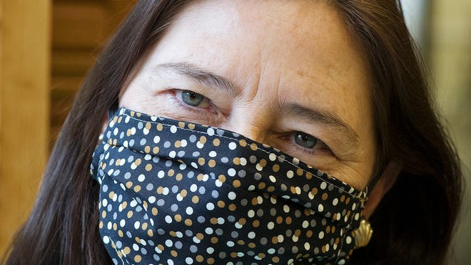 Kathy Hinkle models one of the fabric masks the group is making at First United Methodist Church.