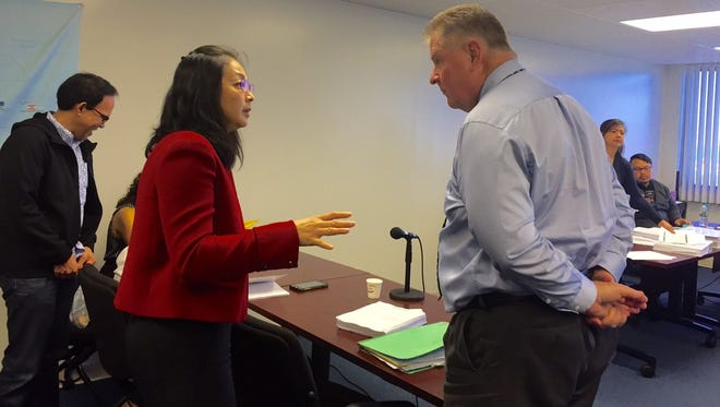 In this file photo, Core Tech International counsel Joyce Tang, left, confers with Assistant Attorney General Tom Keeler, right, counsel for the Department of Public Works.
