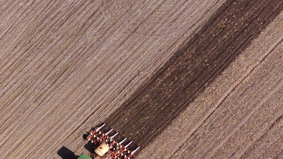 Preparing the field: A farmer doing spring tillage last week near Luther leaves a swath of moist earth behind the equipment as a field is made ready for planting.