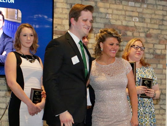 Kyle Whelton, center, is awarded at the Coastal Chamber