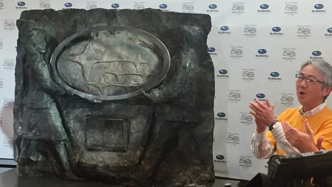 Subaru Chairman Tomomi Nakamura applauds the unveiling of a sculpture at the firm's 50th anniversary celebration Thursday.