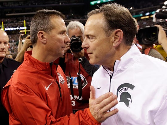 In this Dec. 7, 2013, file photo, Michigan State head coach Mark Dantonio, right, is congratulated by Ohio State head coach Urban Meyer following the Big Ten Conference championship NCAA college football game in Indianapolis.