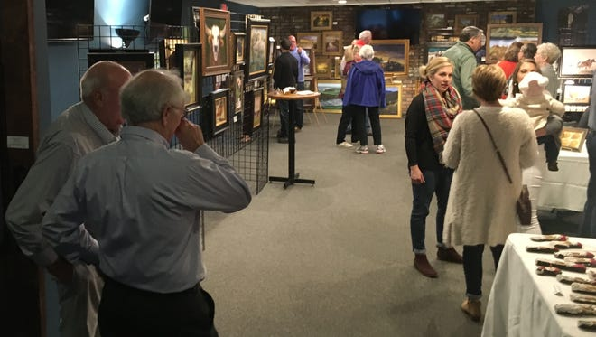 Attendees socialize and peruse the art on display in this file photo from a previous Downtown Henderson Partnership Art Hop.