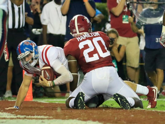 Ole Miss Rebels quarterback Chad Kelly (10) gets up after diving  over the goal as he is hit by Alabama Crimson Tide linebacker Shaun Hamilton (20) at Bryant-Denny Stadium.