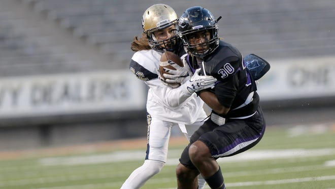 Coronado's Gustavo Holcombe holds on to Franklin receiver Khatib Lyles after his reception last season at the Sun Bowl.