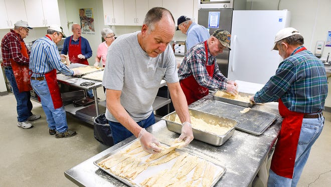 Volunteers bread about 1,200 pieces of fish Thursday, March 2, at the Church of St. Anthony of Padua in preparation for their Friday fish fry. The church uses a secret recipe for the breading.