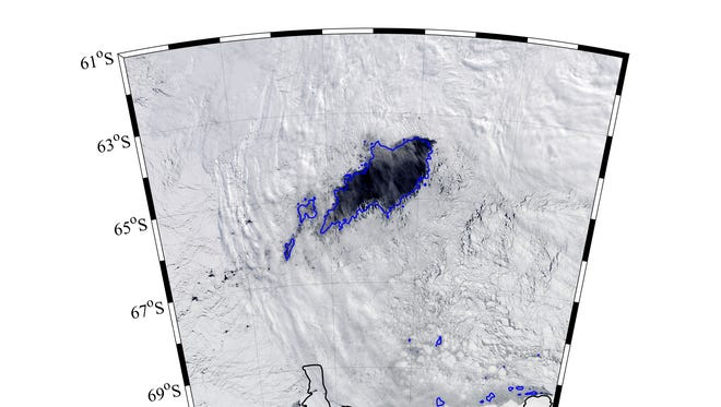 The polynya is the dark region of open water within the ice pack.