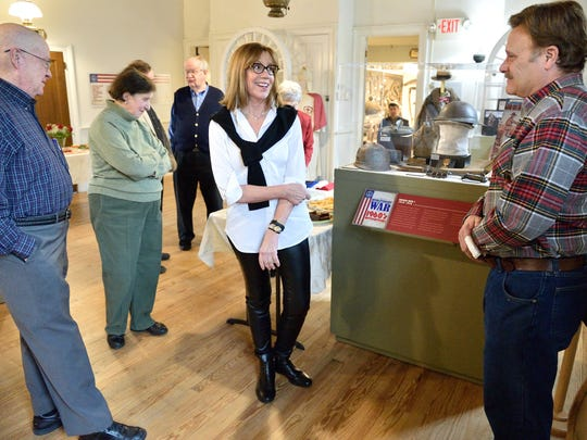 Joy Simmen Hamburger, center, speaking with visitors taking in an exhibit involving artifacts from World War I, is the curator of the From the Revolutionary War to the 1960s Revolution exhibit at the Schoolhouse Museum in Ridgewood.