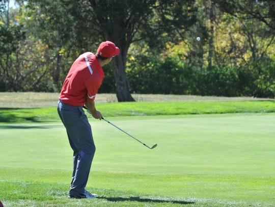 Josh Dentinger chips towards the pin on the 16th hole