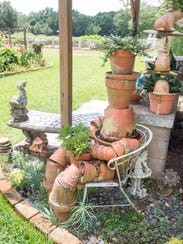 A sculpture of repurposed flower pots create a seated person in Stan and Debbie Barnard's gardens at their home during last year's Secret Garden Tour. This year's event will feature six local gardens with tours Saturday and Sunday.