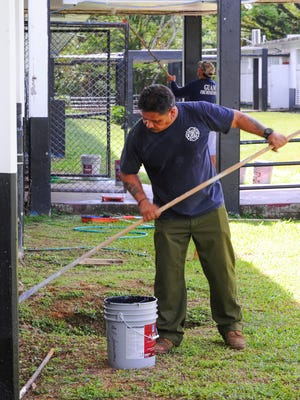 Guam Fire Department firefighters volunteer their time to paint sections of Agueda I. Johnston Middle School on Thursday, July 16.