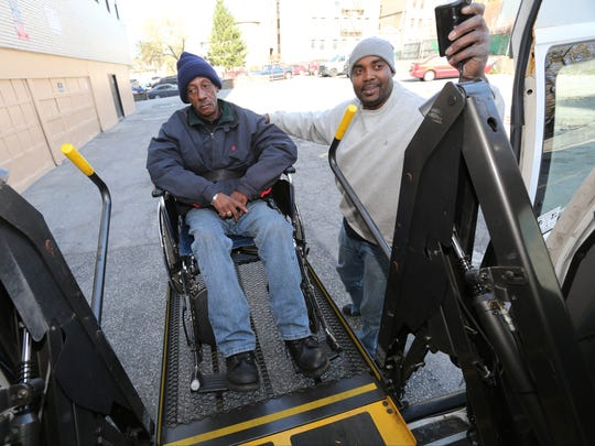 Samora Higgins, right, a driver with RV Ambulette in Yonkers, lowers passenger James Gaddy from the van.