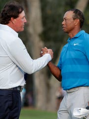 Phil Mickelson, left, and Tiger Woods shake hands after