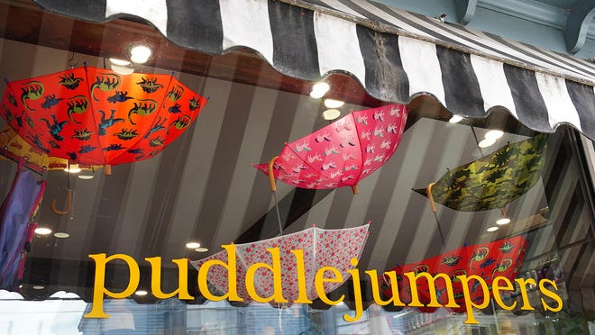 Umbrellas hang from the ceiling and more boots march across the tops of the cases at Puddlejumpers on Water Street in Exeter.