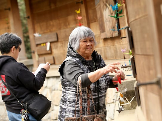 Frances Ikegami, of Bremerton, hangs a string of cranes on the section of the memorial that bears the names of her and her and the rest of the Kitamoto family at the Bainbridge Island Japanese American Exclusion Memorial on Bainbridge Island on Friday. Ikegami was 5 years old when she was forced to leave her home on the island.
