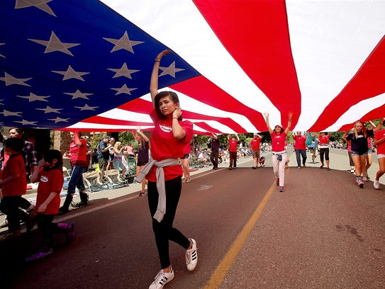 A giant American flag is carried down Madison Ave.