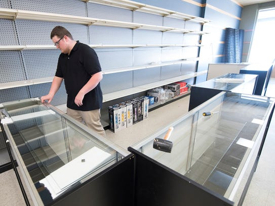 Drew Black assembles shelves while preparing for the opening of Discount Mart. The new store will open the first week of May in the Lincoln Way East shopping center, 1672 Lincoln Way East, Chambersburg.