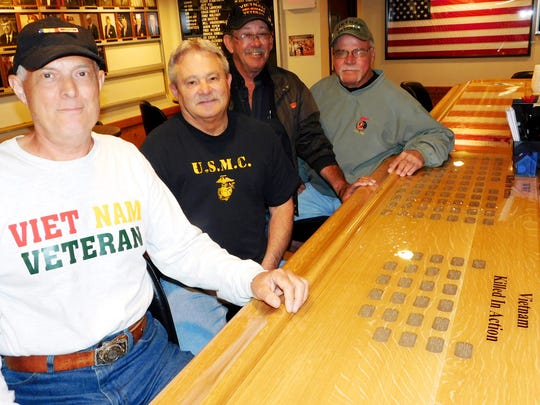 VFW members Randy Miller, Bill Druckenmiller, Jim Schneider and Bill Haas sit along one side of the new post bar which had dog tags for 486 veterans sealed into the top.