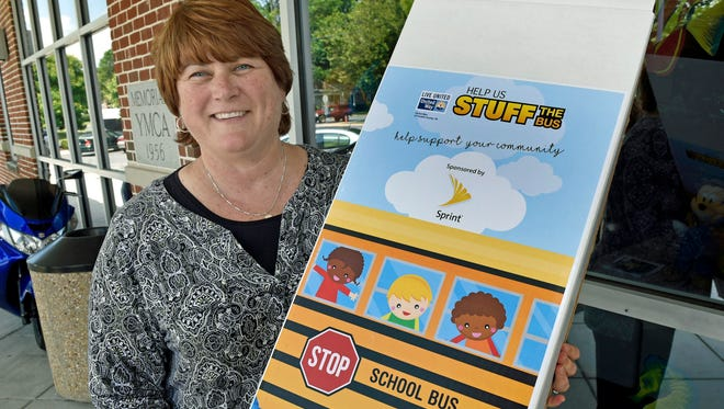 Carla Christian, executive director of Chambersburg YMCA, carries a Stuff the Bus box into the McKinley Street office on Tuesday, July 19, 2016. Stuff the Bus, a United Way program, is distributing boxes to different locations around the county in an effort to collect basic school supplies for children who struggle to have these needs met.