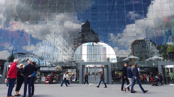 Sky and clouds are reflected in the glass end of the Markthal in Rotterdam.
