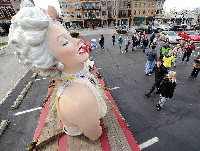 """Jeff and Shari Worrell, of Carmel, walk towards a 26-foot tall Marilyn Monroe sculpture """"Forever Marilyn"""" after it parked at the PNC Bank located on Main Street, Sunday, April 6, 2014, in Carmel. The piece was created by J. Seward Johnson, who created the permeant pieces that are present in Carmel, and is on its way to New Jersey."""