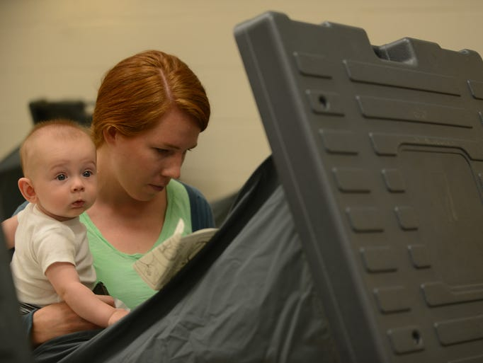 Bridget Winkler (right) hold her son William Winkler, 6 months, (left) as she casts her ballots during early voting July 18 at the agriculture auditorium.