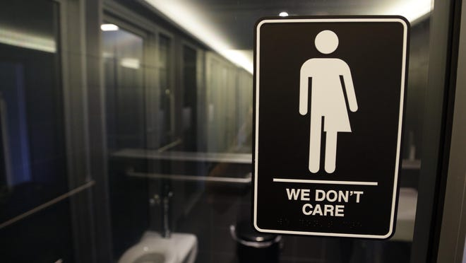 """Asign outside a restroom at 21c Museum Hotel in Durham. The Associated Press has determined that North Carolina's law limiting LGBT protections will cost the state more than $3 billion in lost business over a dozen years.That's despite Republican assurances that the """"bathroom bill"""" isn't hurting the economy."""