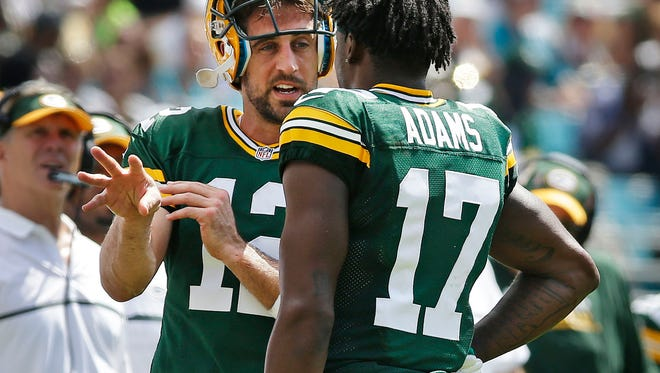 Green Bay Packers quarterback Aaron Rodgers (12)  talks with wide receiver Davante Adams (17) after some miscommunication in the offense ending a  third quarter drive.