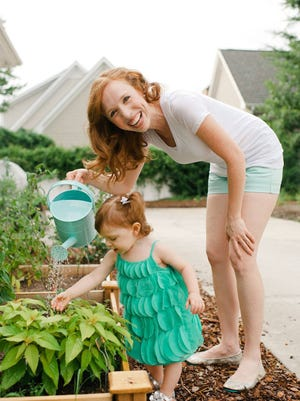 Lara Casey and her daughter Grace Isaacson water their garden.