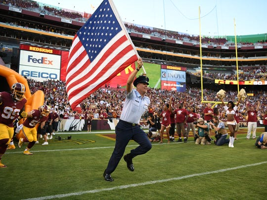Kimball native Isaiah Ehlinger carries the flag onto