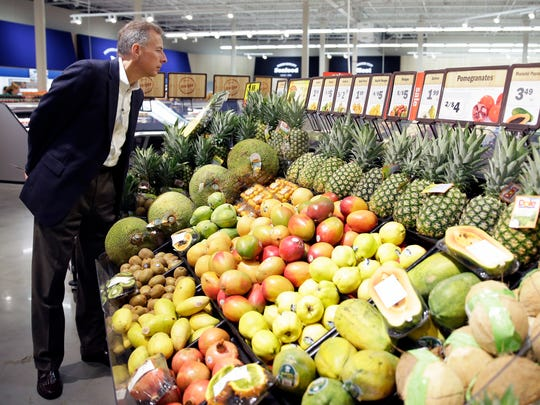 Dan Webb, chief financial officer for Meijer, examines jackfruit for sale Tuesday at the company's new superstore, which opened on Tuesday in Howard.