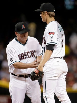 Arizona Diamondbacks manager Chip Hale (3) takes the ball from Arizona Diamondbacks Zack Greinke (21) after a stop in the game against the Philadelphia Phillies during the third inning of a baseball game, Tuesday, June 28, 2016, in Phoenix. Greinke was removed from the game.