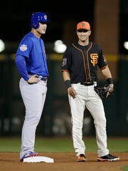 Chicago Cubs first baseman Anthony Rizzo and San Francisco Giants second baseman Joe Panik talk in the first inning at Scottsdale Stadium on Thursday.