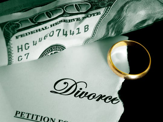 torn divorce decree and cash, with wedding ring