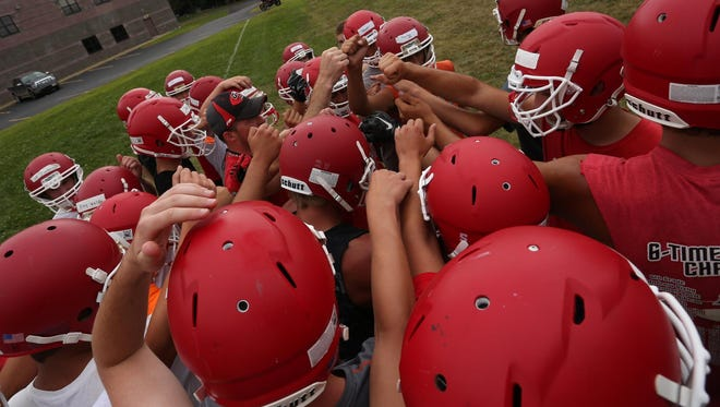 Players gather for a breakdown during the Greenwood Granton practice at Greenwood High School, Tuesday, August 4, 2015.
