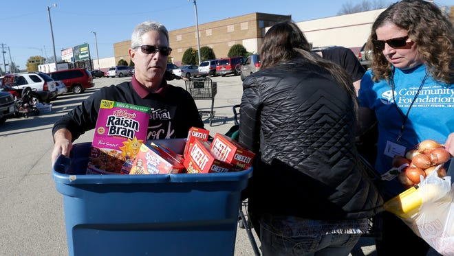 Green Bay Press Gazette news director Robert Zizzo helps distribute food during the 2015 Stock The Shelves campaign kickoff event.